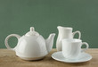 white ceramic coffee set on old wooden table over green backgrou