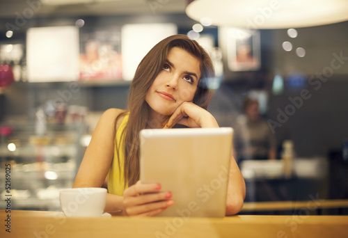 Young woman dreaming in cafe .