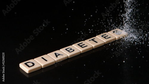 Sugar pouring over letter pieces spelling diabetes
