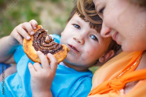 Cute boy eating chocolate snail