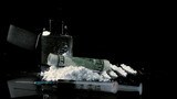 Rolled up dollar note falling on pile of white drug beside syringe and lighter