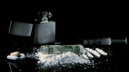 Rolled up dollar note falling on pile of white drug with syringe lighter and tablets