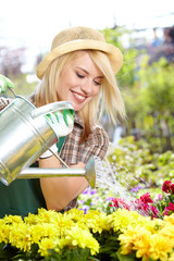 Smiling young woman watering flowers in the flowers market