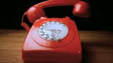 Red receiver falling onto retro dial phone