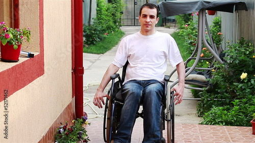 Young man on wheelchair in the yard