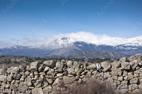 Stone wall. At the background, Guadarrama Mountains, Spain