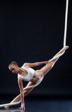 Athletic aerialist posing with rope