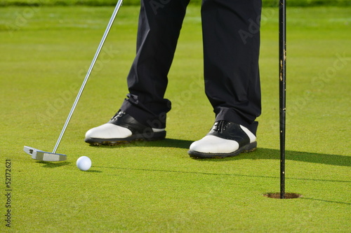 Man playing golf, Golfer Sinking an Early Morning Putt