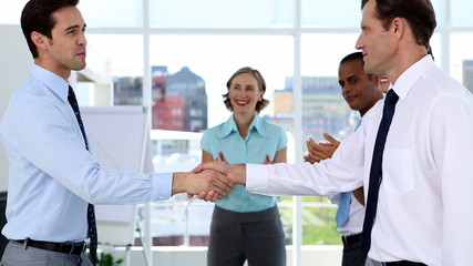 Businessmen shake hands while other business people applauding