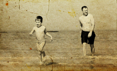 father and son going to swim in the sea. Photo in old image styl