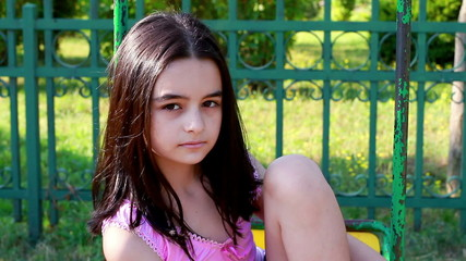 Sad young girl on swing in summer park