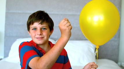 Boy piercing his balloon in the bedroom
