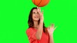 Woman having fun with a basket ball on green screen