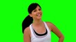 Woman in sportswear tossing her hair on green screen