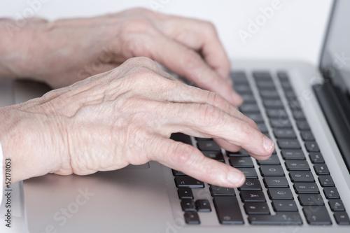 canvas print picture Hände einer älteren Frau tippen auf der Tastatur eines Laptops