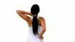 Fit woman stretching her neck and back on white background