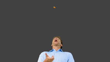 Man catching an orange segment with mouth on grey screen