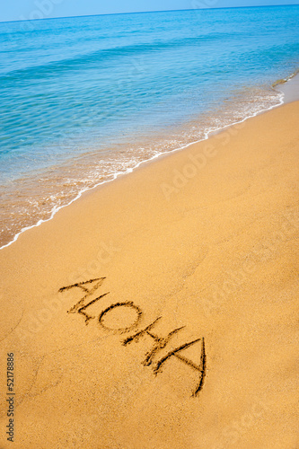 Word Aloha written in sandy on tropical beach