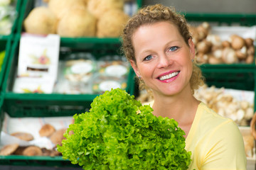 frau kauft salat ein