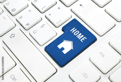 Home or real estate concept, blue house key on a keyboard
