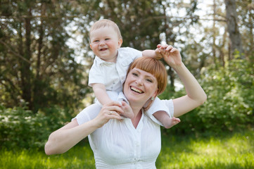 smiling mother holding a child on his shoulders