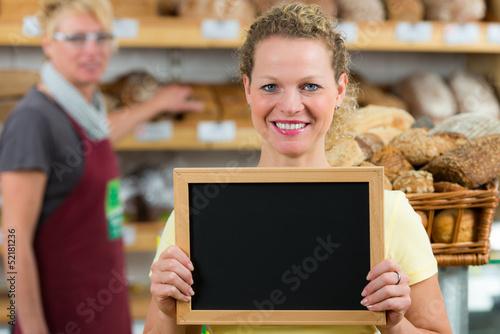 bäckereifachverkäuferin mit hinweistafel