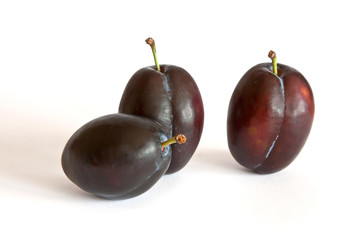 Group of purple plums isolated on a white