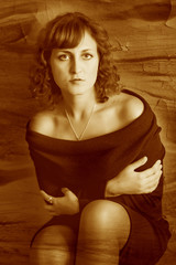 retro sepia photo curly girl woman in a brown dress sits near th
