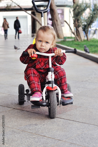 baby on her  tricycle