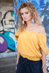 Dreamy hip teenage blonde woman standing by graffiti wall
