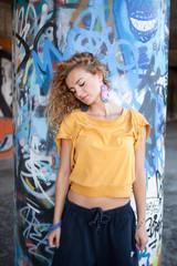 Beautiful hip teenage blonde woman standing by graffiti wall