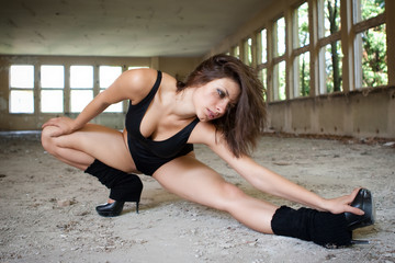 Woman in black leotard and high heels, dancing in old building
