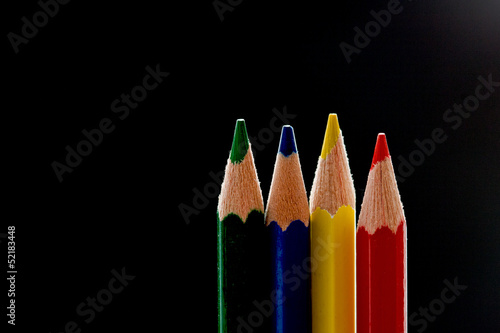 Four primary color pencils before black background