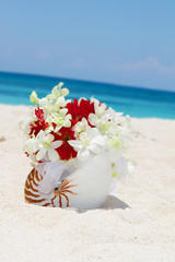 bridal bouquet with wedding rings in a shell on sand tropical be