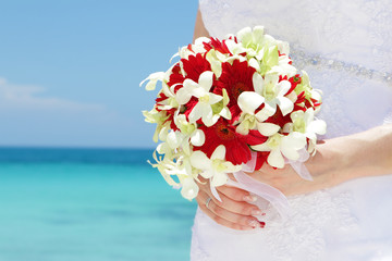 bride holding bridal bouquet on natural sea background