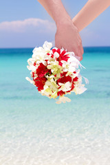 bride and groom holding bridal bouquet on natural sea background