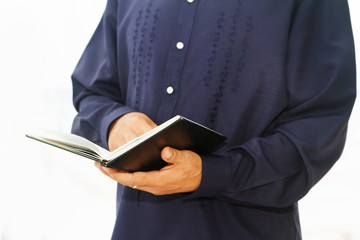pastor priest reading holy bible isolated over white