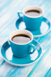 Vertical shot of two turquoise espresso cups on wooden boards