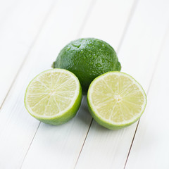 Ripe lime and its halves on wooden boards, close-up