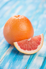 Studio shot of ripe grapefruit and its segment on wooden boards