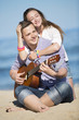 Portrait of young man with guitar and woman on a beach