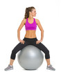 Smiling fitness woman on fitness ball looking on copy space