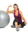 Happy woman sitting near fitness ball and showing muscles