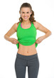 Happy fitness young woman showing flat belly