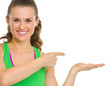Happy fitness young woman presenting something on empty palm