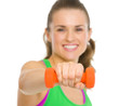 Closeup on happy fitness woman making exercise with dumbbells