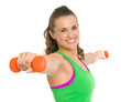 Smiling fitness young woman making exercise with dumbbells