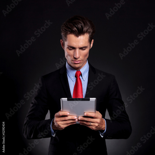 business man looks at tablet