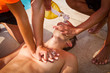 CPR, Man receiving cardiopulmonary resuscitation close to a swimming pool. - 52192624