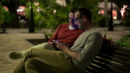 Young male friends with smartphone in the city